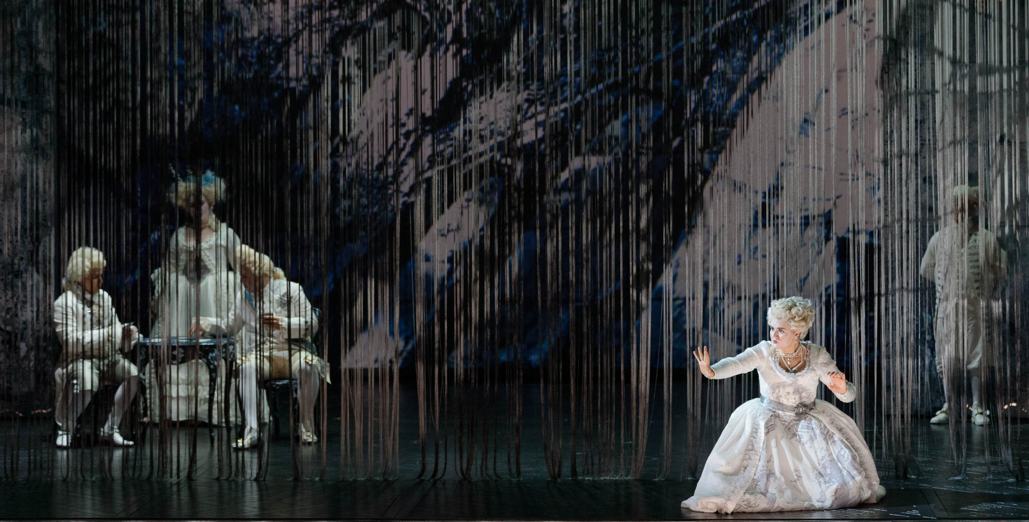 Woman crouches down in front of scenery in the 2019 production of The Ghosts of Versailles.