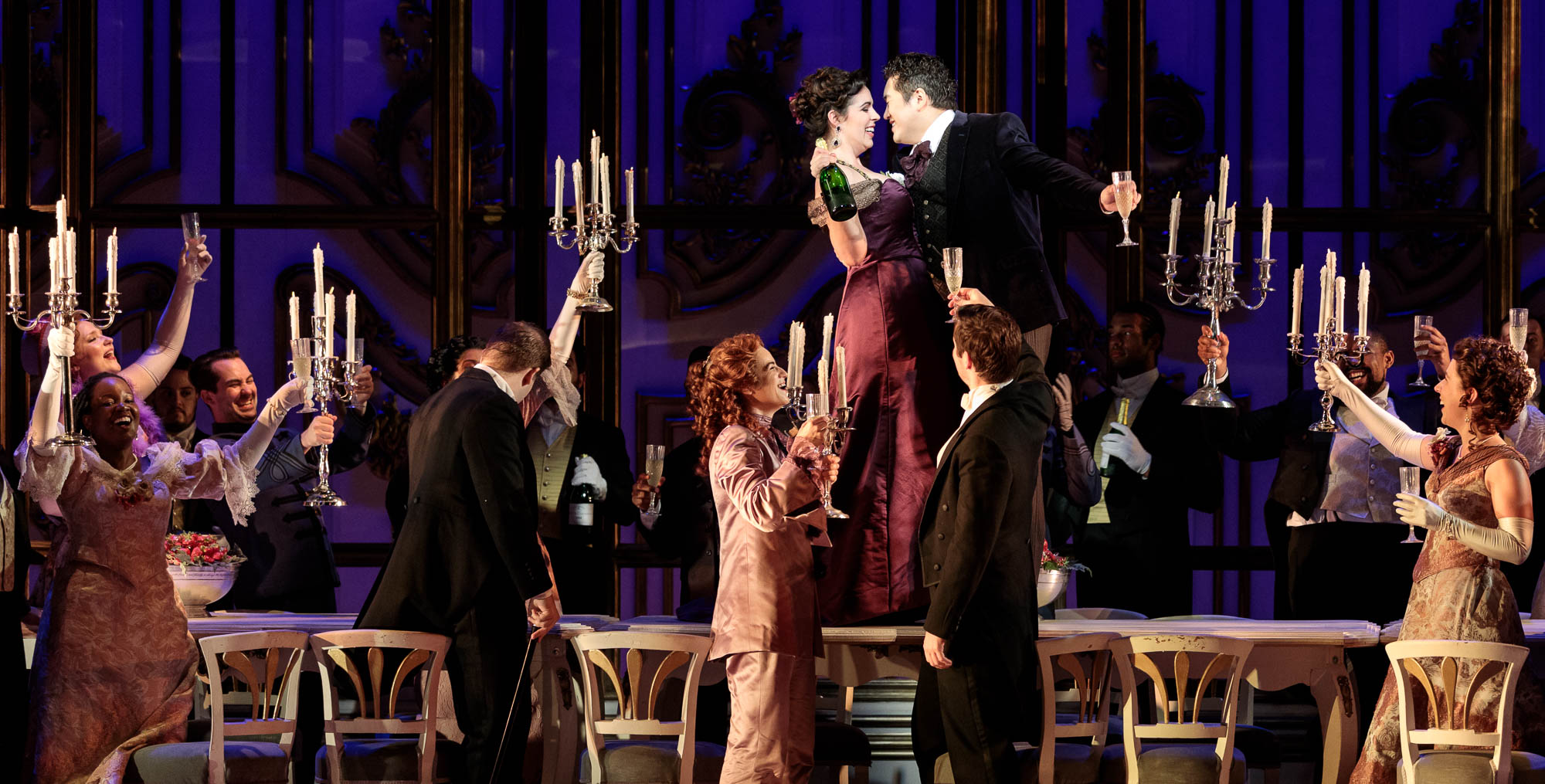 Cast raises candles to couple, center, in the 2019 production of La traviata.