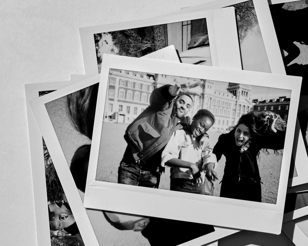 Close-up of Polaroid photos of group of friends enjoying day showing peace sign at camera. Photo: Guille Faingold.