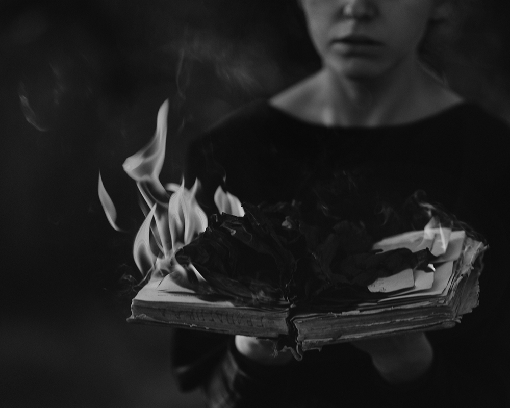Woman holds an open book on fire. Photo: Jurij Krupiak.