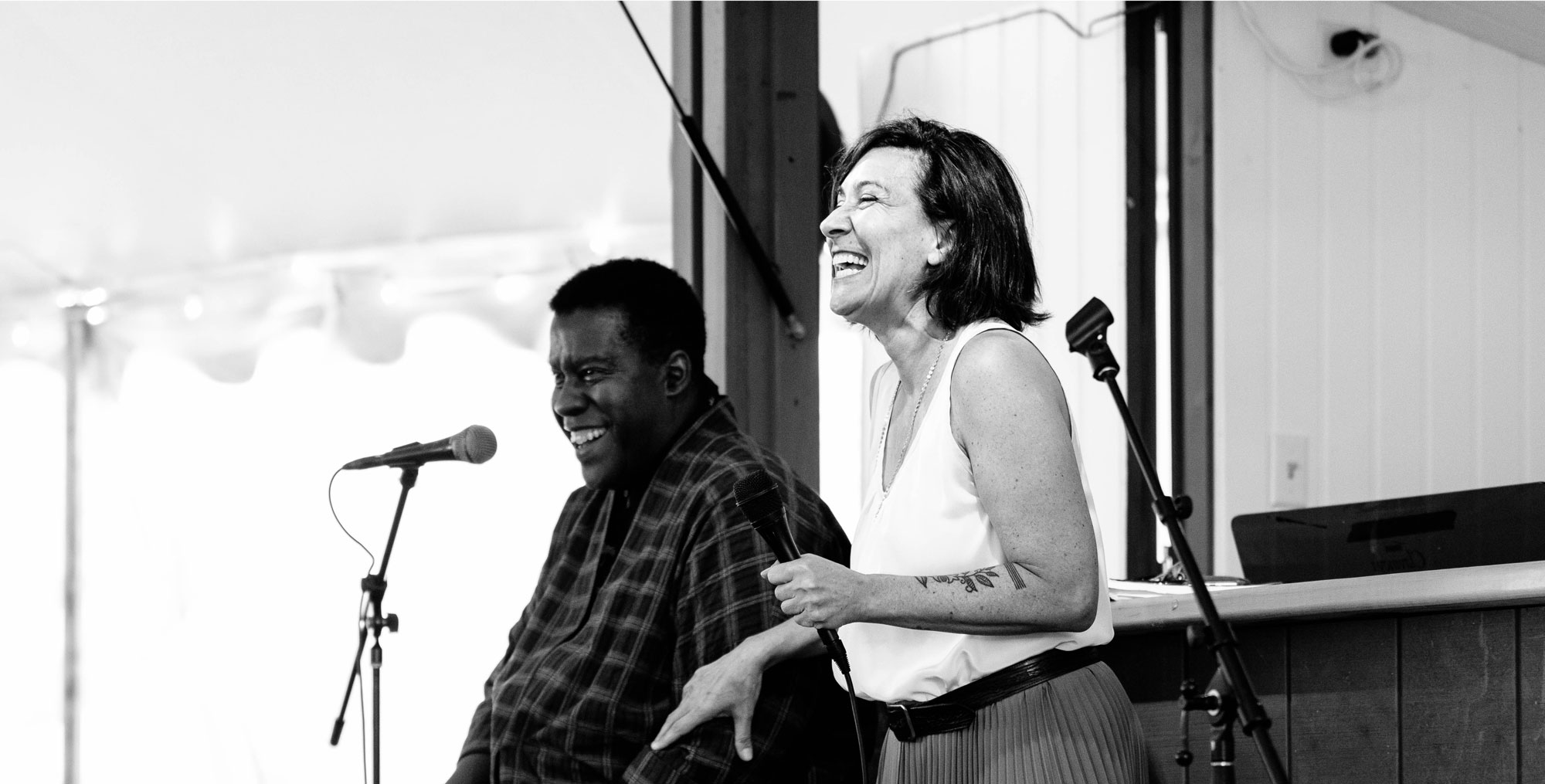 Two speakers laugh while giving a preview talk. Photo: Karli Cadel.