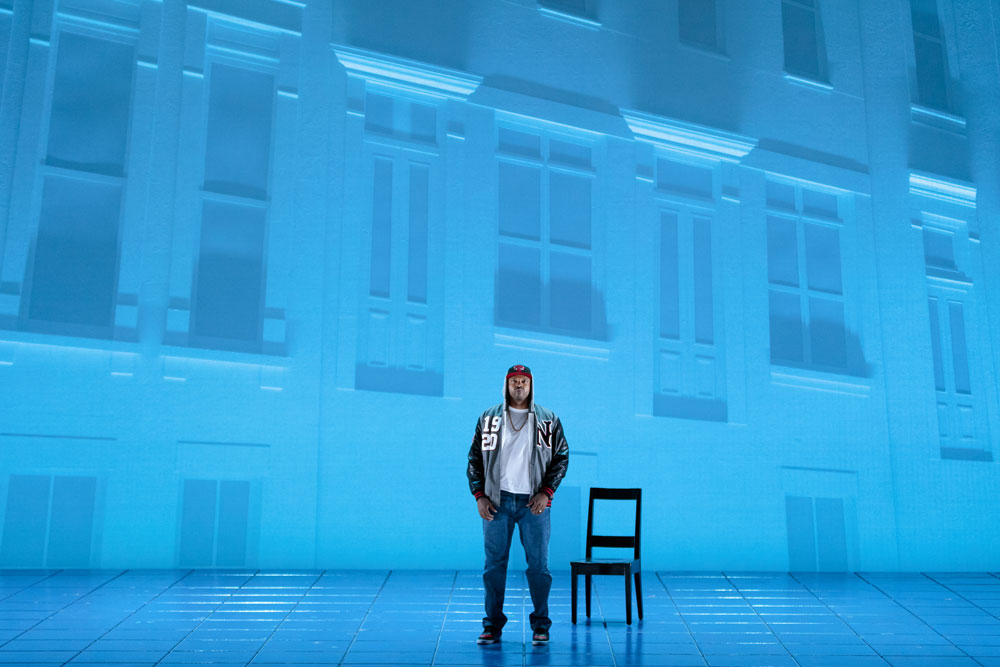 Man stands center stage next to a chair for the 2019 production of Blue.