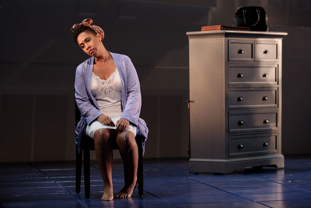A woman leans in her chair looking down in remorse for the 2019 production of Blue.