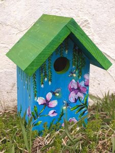 Small wooden birdhouse beautifully painted with flowers on the front.