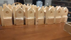 Wooden birdhouse kits assembled and ready to be distributed.