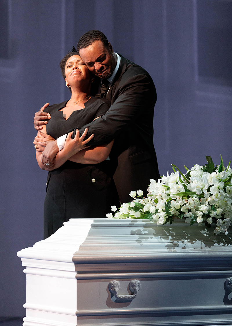 Image of the performance of Blue. The Father holds the Mother next to a white casket. They have expressions of grief on their faces.