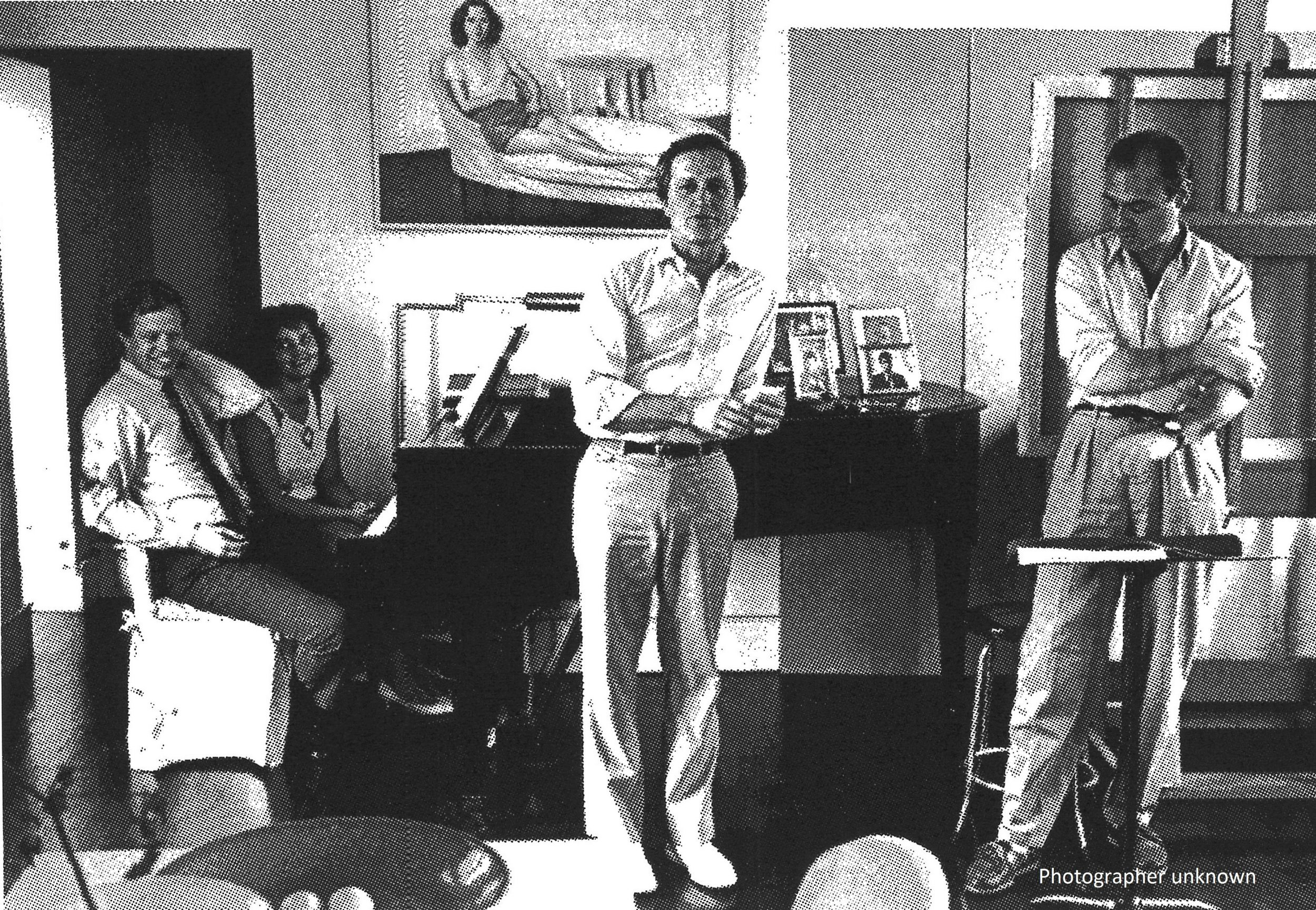 Paul Kellogg leans on a piano. There is a painting of a woman on the wall behind him. To his right and left are men. A woman sits at the piano
