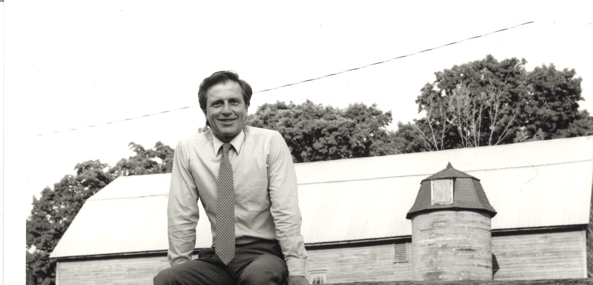 Black and white photograph; Paul Kellog sits on a wooden picket fence, wearing button-down shirt and tie. A barn silo appears behind him.