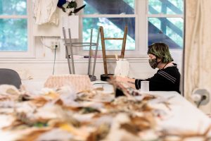 A costume technician works on a sewing machine in the background of the costume shop, a sunny day in the forrest is seen outside the windows behind her. The foreground is blurred but a table is filled with blurry feathers.