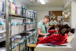 A costume technician in a teal blouse stands at a work table in the costume shop looking at fabric samples with boxes of fabric stacked on the shelves behind them..