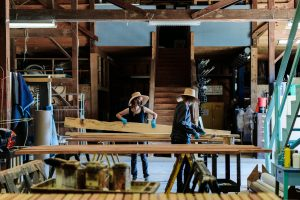 Inside one of the barns on the Glimmerglass campus, two scenic artists wearing large sun hats work on wooden boards and lift them while wearing blue nitrile gloves.