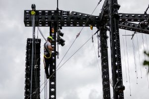 An audio technician wearing a lime green hard hat and in a harness is clipped in a tethered to the black outdoor stage trussing 15 feet iff the ground. The sky is moody and cloudy. The structure includes diagonal aircraft cables, large speaker arrays, chain motors, safety equipment, and strings of lights.