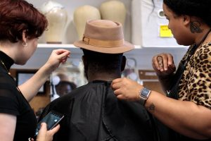 A member of the cast sits in the Hair & Makeup room flanked on either side by two Hair & Makeup supervisors. They are adjusting a tan hat on top of the performers head.
