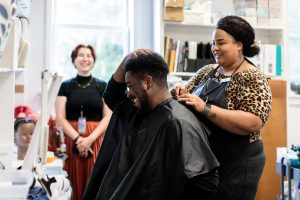 A performer checks out his hair after two Hair & Makeup technicians finish a style for the upcoming production.