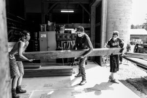 Three members of the production crew, all wearing face masks, unload long pieces of lumber from a black pickup truck, and carry it into the paint barn on the glimmerglass campus. The photo is black and white.