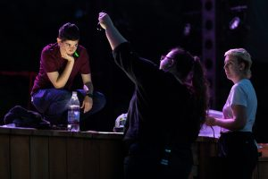 Three members of the lighting staff discuss lighting angles at the edge of the stage. One on the left of the frame kneels on the stage, hand propping their head up, looking towards the two standing at the ground at the edge of the stage. The Technician at center is pointing up towards the pink light shining on the three of them.