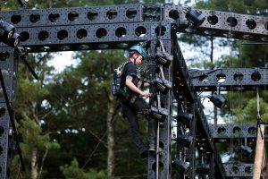 A lighting technician wearing a blue hard hat, all black clothing, and a harness, repels from the top of the outdoor black truss structure in order to hang and adjust PAR lighting equipment.