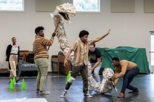 Inside the Glimmerglass Rehearsal Room, three chorus members carry a long white feathery snake puppet that curves around the performer playing Tamino. His arm is stretched out forward and his gaze follows his hand.