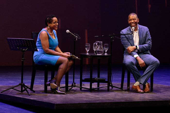 Photograph of Teresa Miller sitting in a chair across from Ta'Nehisi Coates on stage.