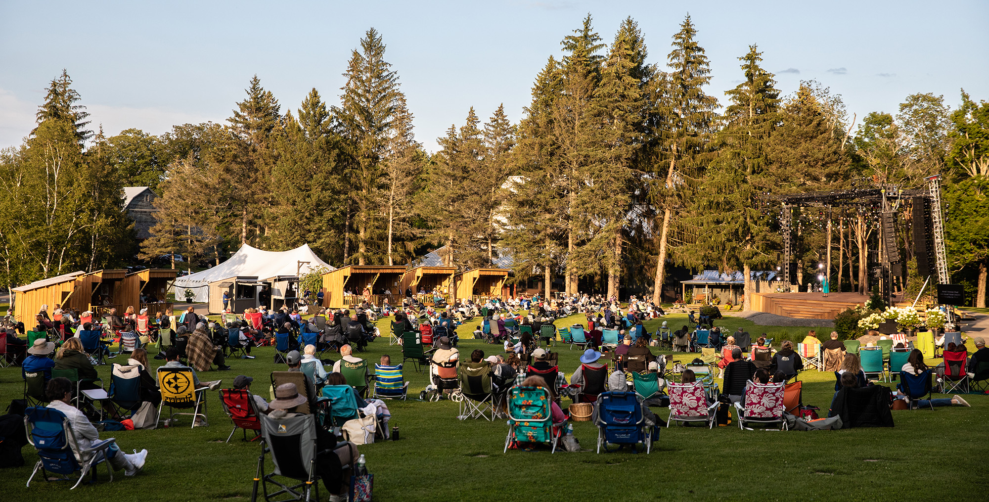 A photograph of The Glimmerglass Festival lawn; the lawn is filled with people sitting in different colored lawn chairs; a stage is seen off to the right.
