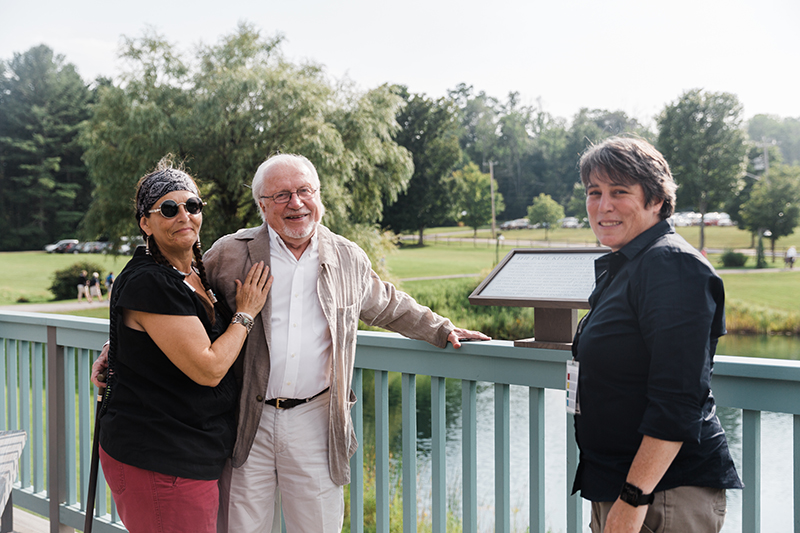 Three people stand in front of a plaque, looking at the camera; to the left is a woman in a black shirt and red pants with a scarf wrapped around her head; she wears sunglasses and has her arm on the chest of an older gentleman who is smiling at the camera. To the right is a woman in a black shirt with short black hair.