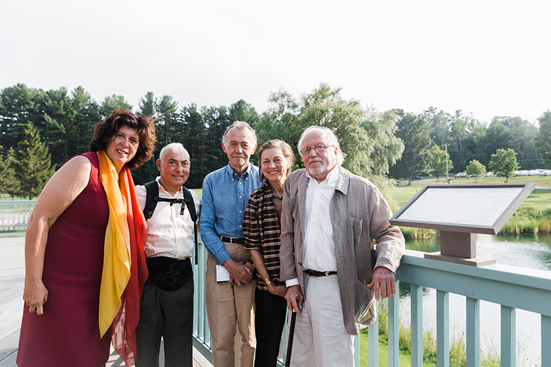 A group photo; five people look at the camera, left is Francesca Zambello in a black dress with an orange scarf, then a shorter man in a white shirt and blank pants, a man in a blue shirt and tan pants, a woman with a plaid dress and then an older gentleman; they are outside on a sunny day with greenery behind them.